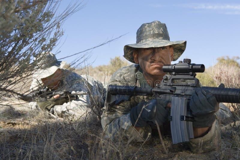 Soldados que apontam rifles no campo fotografia de stock