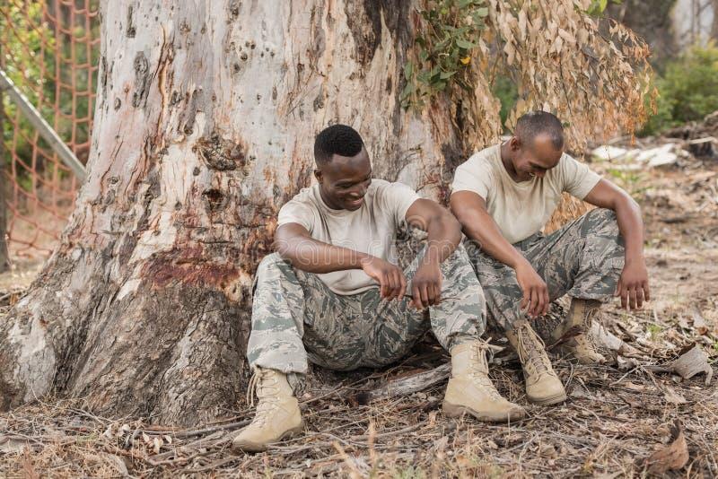 Soldados que têm uma conversação durante o treinamento do curso de obstáculo imagens de stock