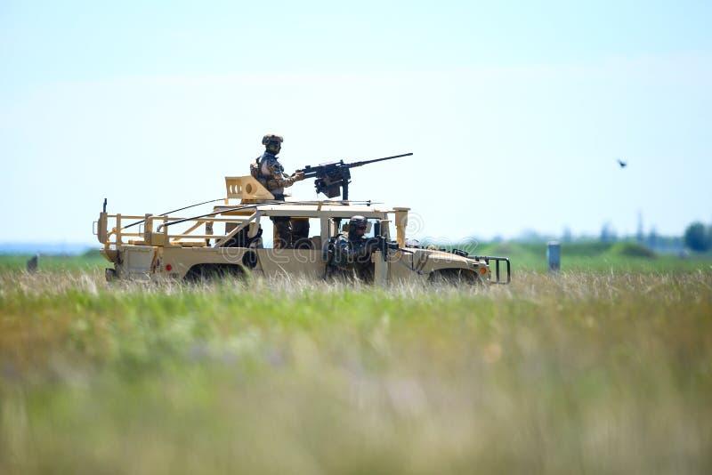 Soldados romenos usam um veículo blindado Humvee num campo, num dia de verão ensolarado durante uma furadeira imagens de stock