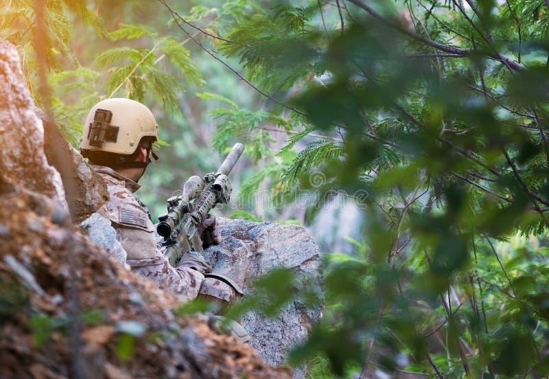 Soldados totalmente equipados que llevan al enemigo que ataca uniforme del camuflaje, jugador militar del juego de Airsoft en uni fotos de archivo libres de regalías