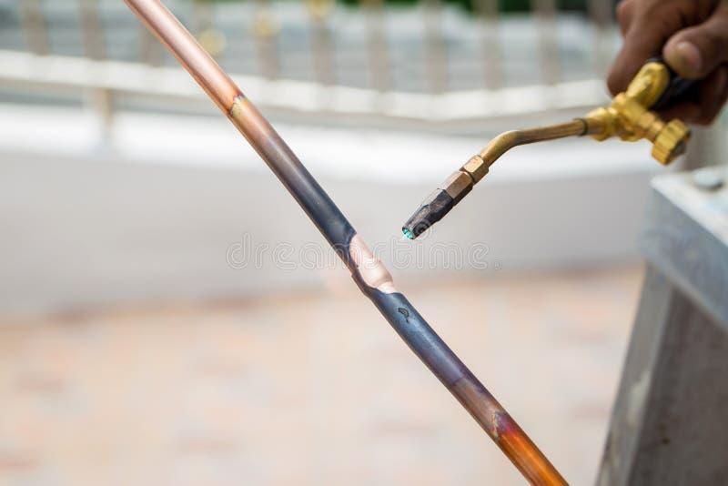 Soldadura del tubo de cobre de una tubería de gas metano o de un condicionamiento o de un circuito de agua Tubos de cobre que sue fotos de archivo
