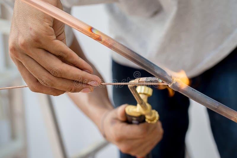Soldadura del tubo de cobre de una tubería de gas metano o de un condicionamiento o de un circuito de agua Tubos de cobre que sue imágenes de archivo libres de regalías