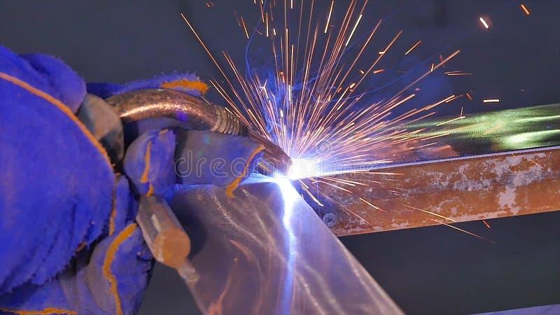 Soldadura do metal com faíscas e fumo Trabalhador com metal de soldadura da máscara protetora O soldador junta-se às peças de met fotografia de stock