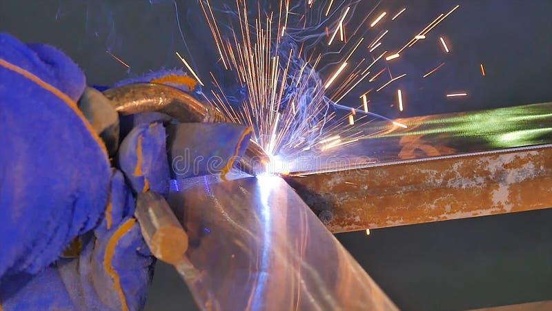 Soldadura do metal com faíscas e fumo Trabalhador com metal de soldadura da máscara protetora O soldador junta-se às peças de met imagem de stock royalty free