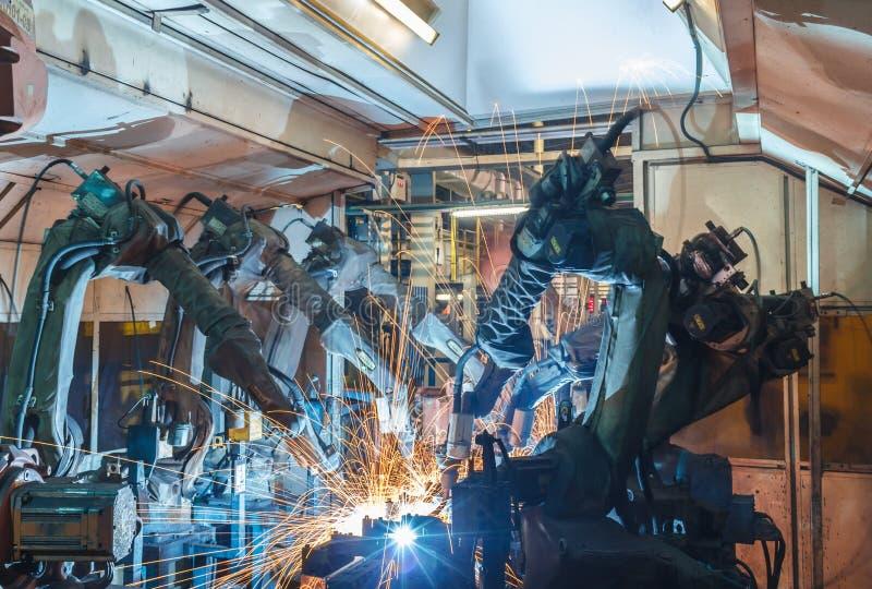 A soldadura do robô em uma fábrica das peças de automóvel fotos de stock