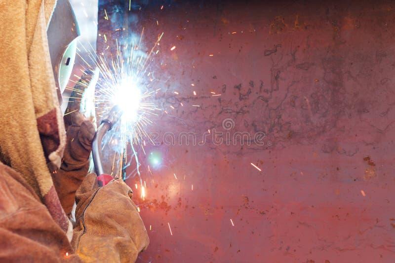 Soldadura do trabalhador em uma fábrica Solda em uma planta industrial imagem de stock