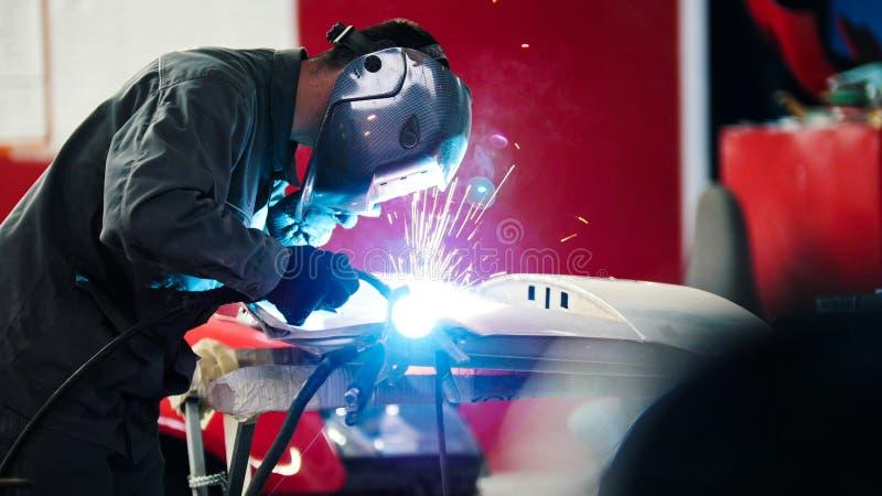 Soldadura industrial: trabajador en el detalle en servicio auto del coche - bengalas azules de la reparación del casco imagen de archivo libre de regalías