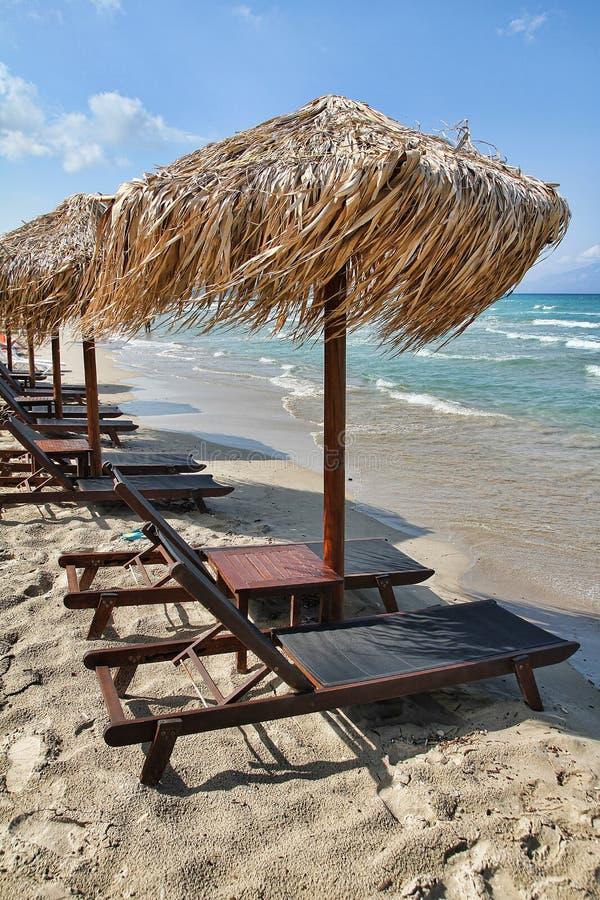 Soldagdrivare och paraplyer på stranden royaltyfri bild