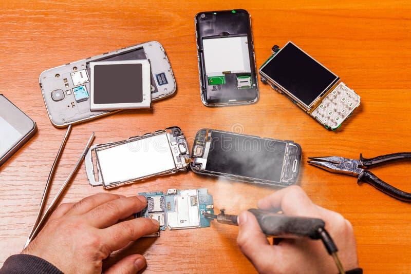 Soldando, repare telefone quebrado imagem de stock
