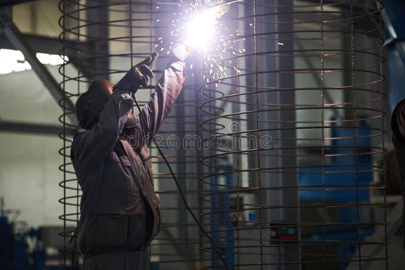 Soldas do homem do soldador na fábrica fotos de stock royalty free