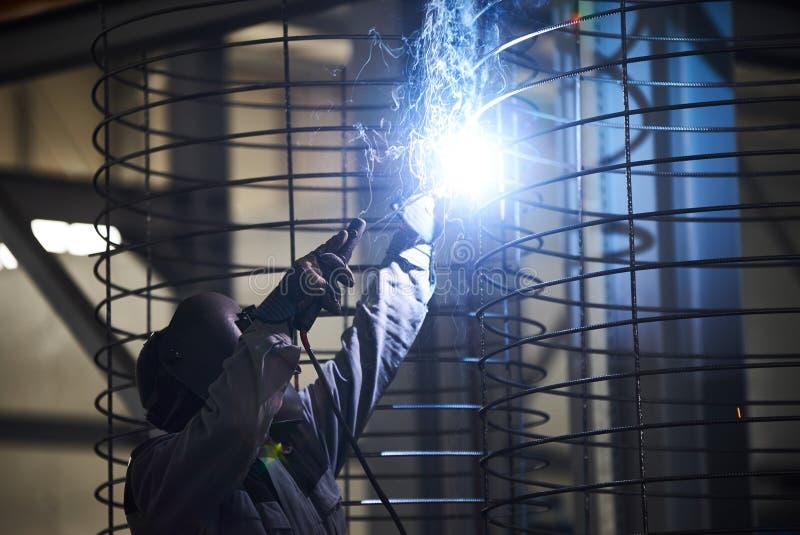 Soldas do homem do soldador na fábrica foto de stock