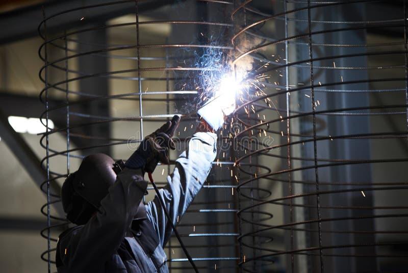 Soldas do homem do soldador na fábrica imagens de stock royalty free