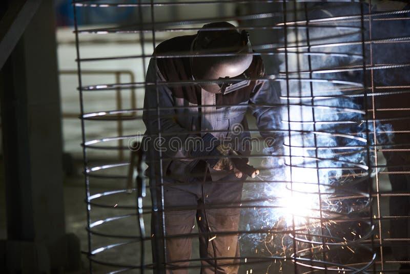 Soldas do homem do soldador na fábrica imagem de stock