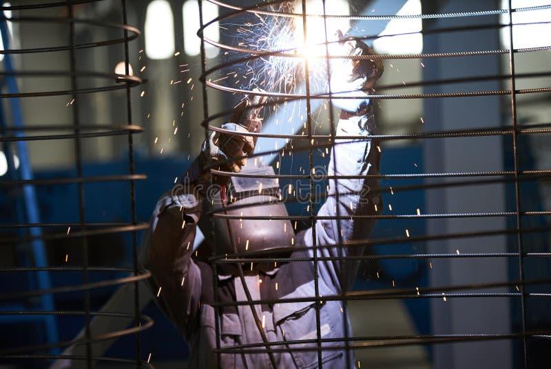 Soldas do homem do soldador na fábrica imagens de stock