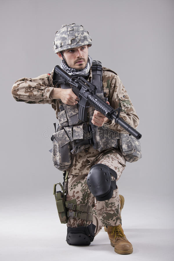 Soldat à genoux avec la mitrailleuse photographie stock