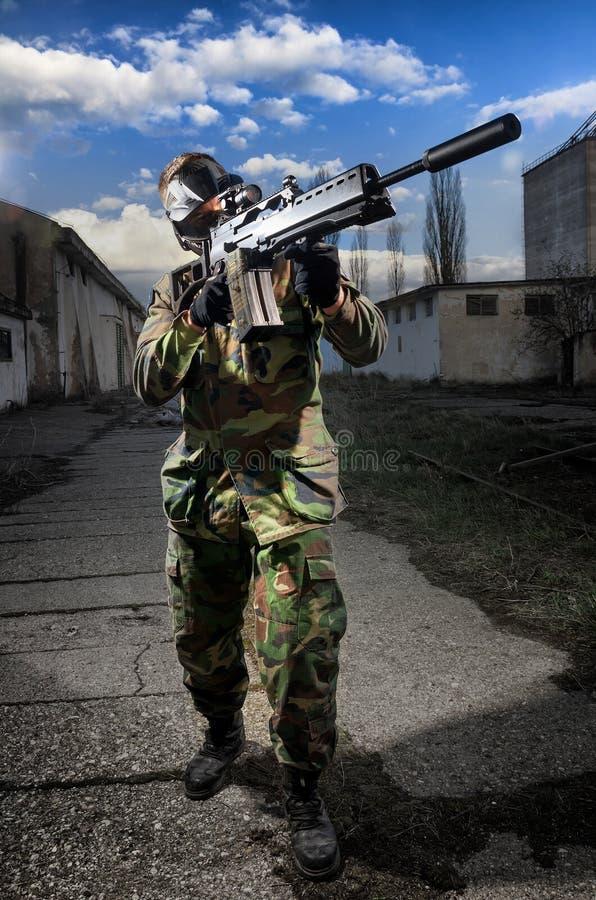 Soldat airsoft, das eine Waffe zielt durch den Bereich hält stockfoto