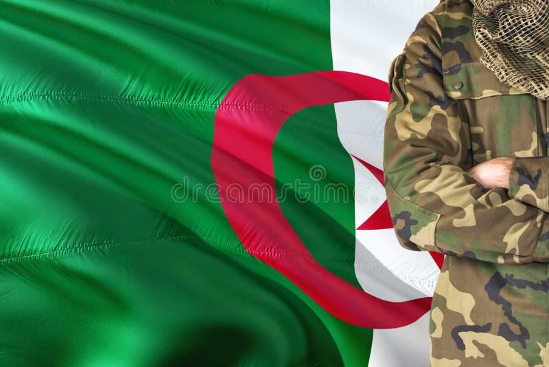 Soldat algérien croisé de bras avec le drapeau de ondulation national sur le fond - thème militaire de l'Algérie images libres de droits