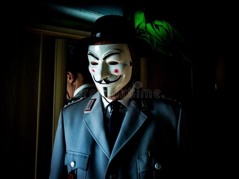 Soldat allemand dans l'uniforme avec le masque de fawkes de type sur le visage photographie stock libre de droits