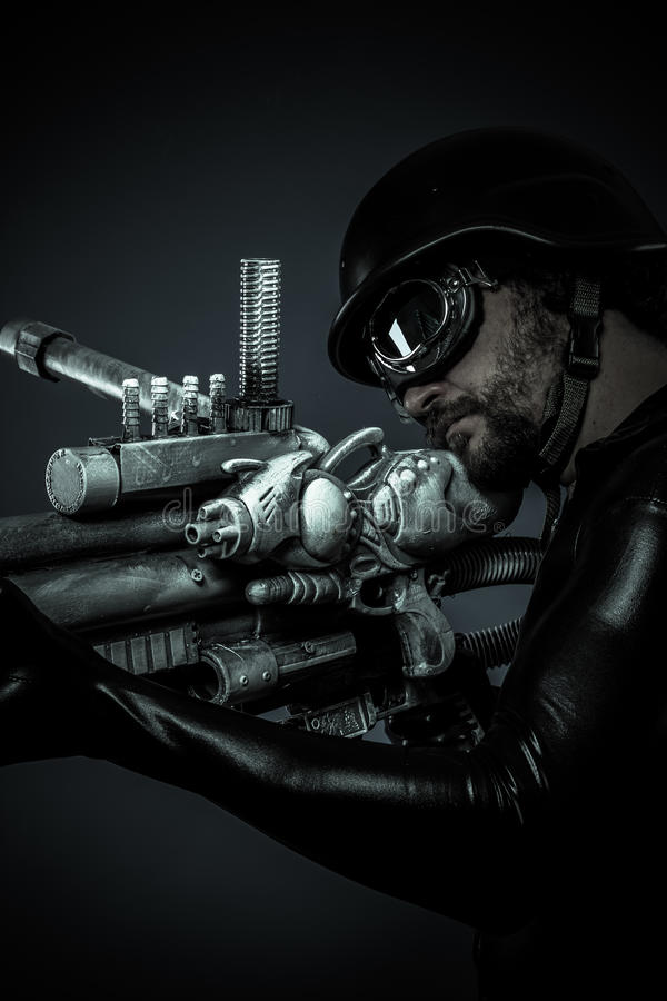 Soldat av framtiden med det enorma den laser-vapnet och kanonen som pekar arkivbilder