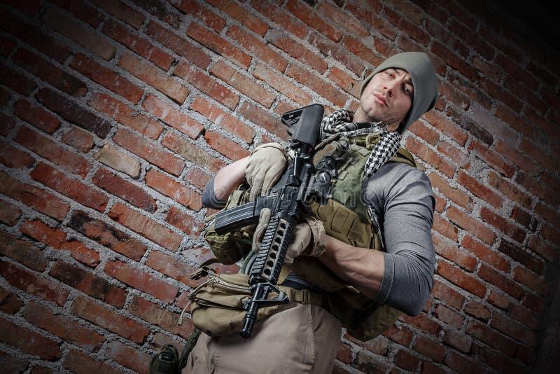 Soldat avec le fusil regardant l'appareil-photo photographie stock libre de droits