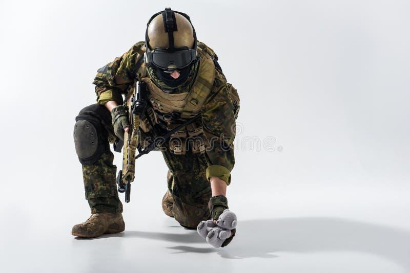 Soldat calme observant à l'ours de nounours photos stock