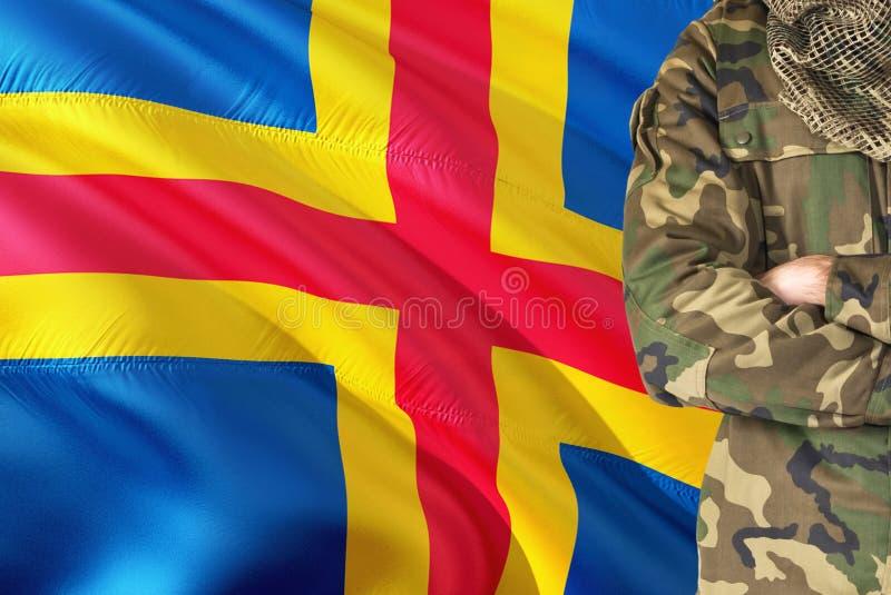 Soldat croisé de bras avec le drapeau de ondulation national sur le fond - thème militaire d'îles d'Aland images stock