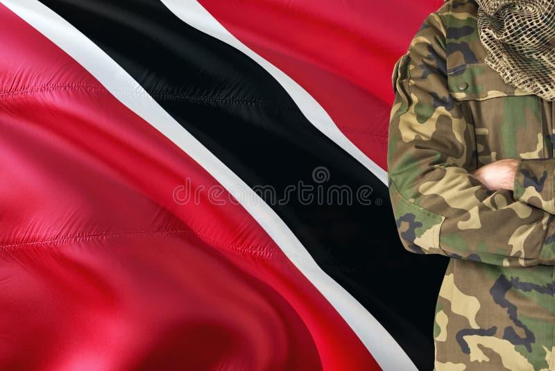 Soldat croisé de bras avec le drapeau de ondulation national sur le fond - thème de Trinidad And Tobago Military photos stock