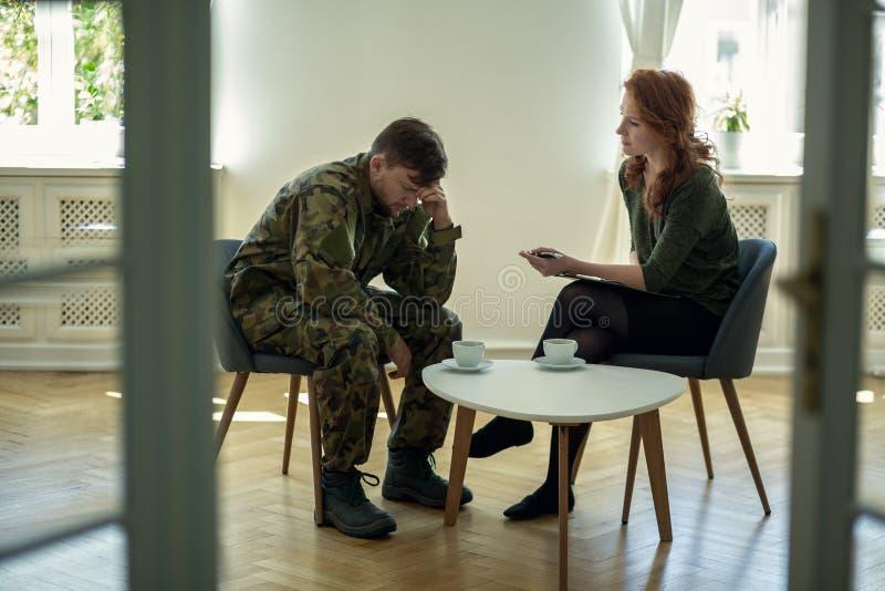 Soldat déprimé et son psychothérapeute pendant une session Vue par une porte photographie stock