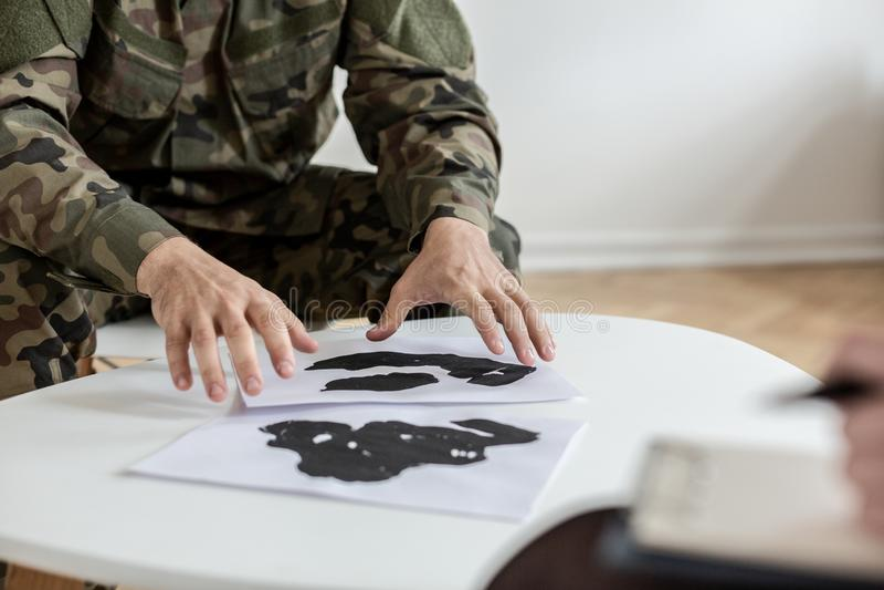 Soldat dans l'uniforme vert de moro choisissant des photos pendant la thérapie avec le psychiatre image libre de droits