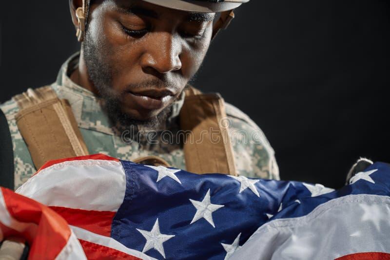 Soldat dans le casque regardant tristement le drapeau national photographie stock libre de droits