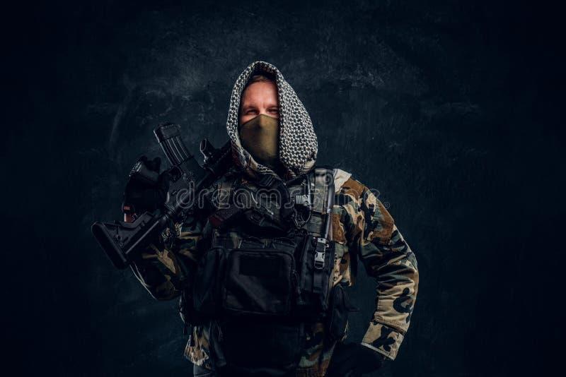 Soldat de forces spéciales dans le masque de port d'uniforme militaire et capot posant avec un fusil d'assaut photo stock