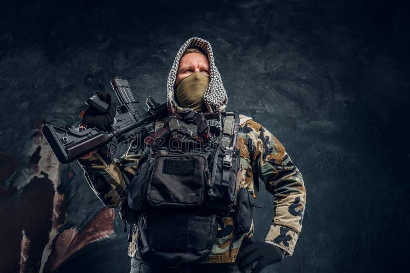 Soldat de forces spéciales dans le masque de port d'uniforme militaire et capot posant avec un fusil d'assaut photographie stock