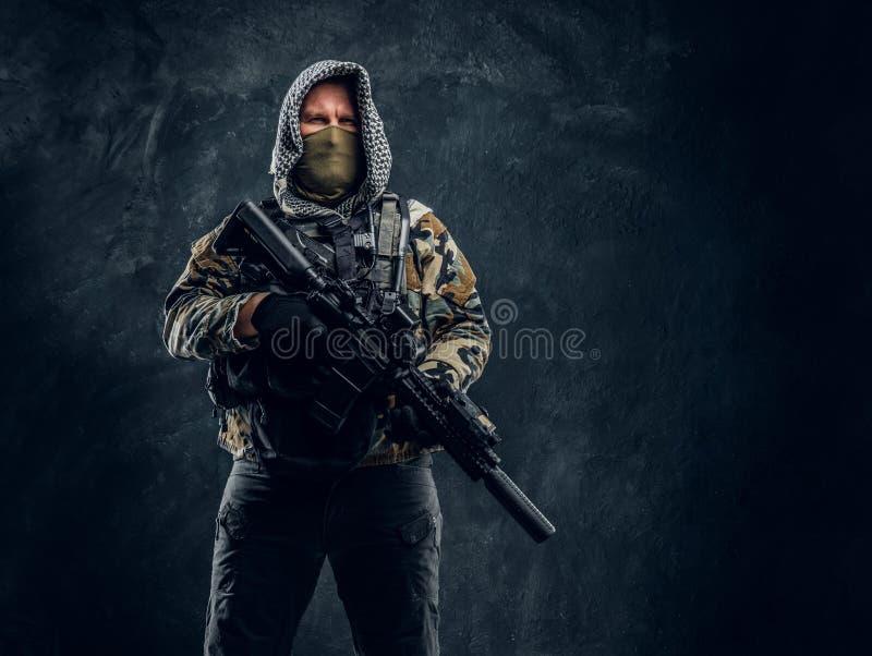 Soldat de forces spéciales dans le masque de port d'uniforme militaire et capot tenant un fusil d'assaut photo libre de droits