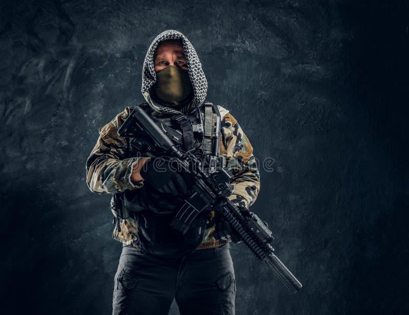 Soldat de forces spéciales dans le masque de port d'uniforme militaire et capot tenant un fusil d'assaut photographie stock