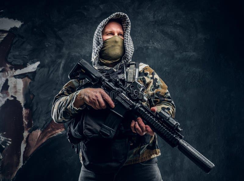 Soldat de forces spéciales dans le masque de port d'uniforme militaire et capot tenant un fusil d'assaut photo stock