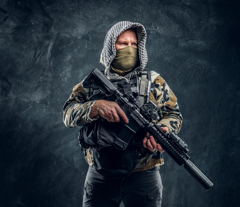 Soldat de forces spéciales dans le masque de port d'uniforme militaire et capot tenant un fusil d'assaut images stock