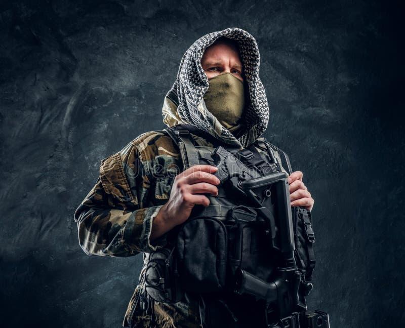 Soldat de forces spéciales dans le masque de port d'uniforme militaire et capot tenant un fusil d'assaut image libre de droits