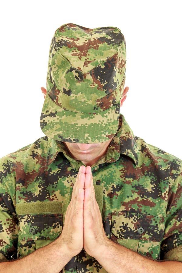 Soldat de guerre priant dans l'uniforme de camouflage de militaires avec l'arc principal images libres de droits