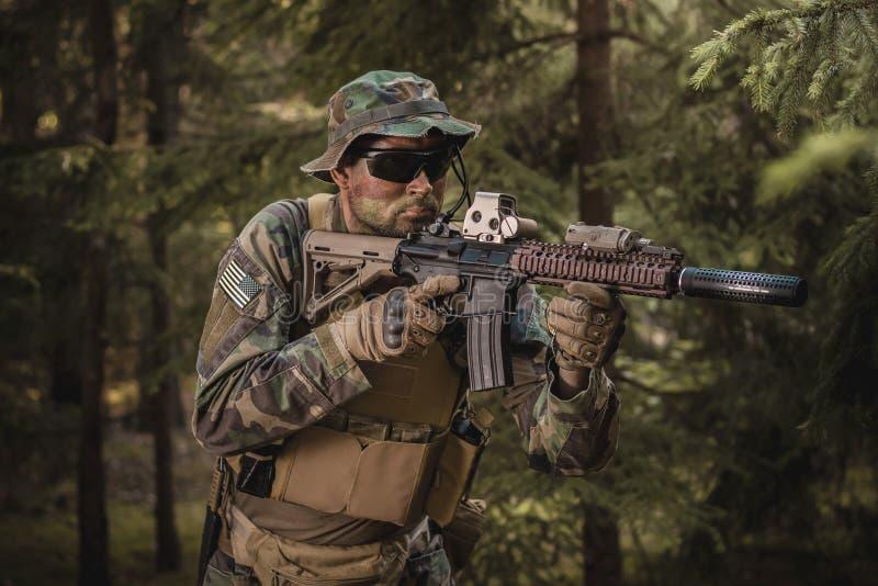 Soldat der besonderen Kräfte, der in den Wald zielt stockfotos