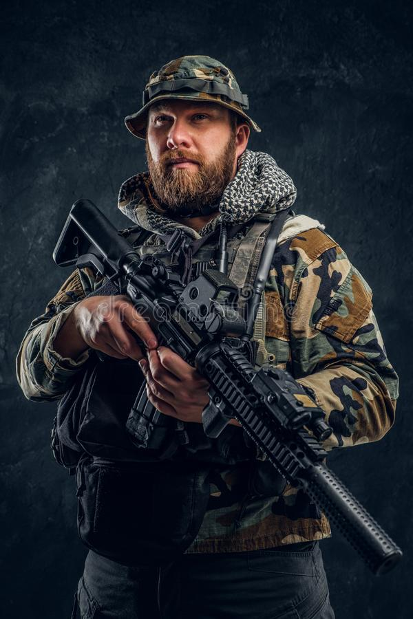 Soldat der besonderen Kräfte in der getarnten Militäruniform, die ein Sturmgewehr hält Studiofoto gegen eine Dunkelheit lizenzfreie stockfotos