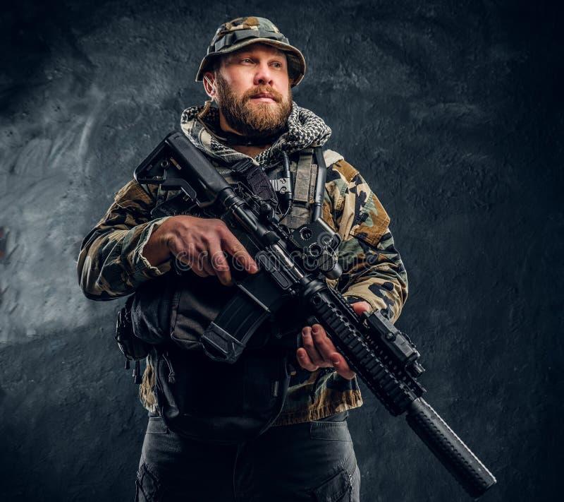 Soldat der besonderen Kräfte in der getarnten Militäruniform, die ein Sturmgewehr hält Studiofoto gegen eine Dunkelheit lizenzfreie stockfotografie
