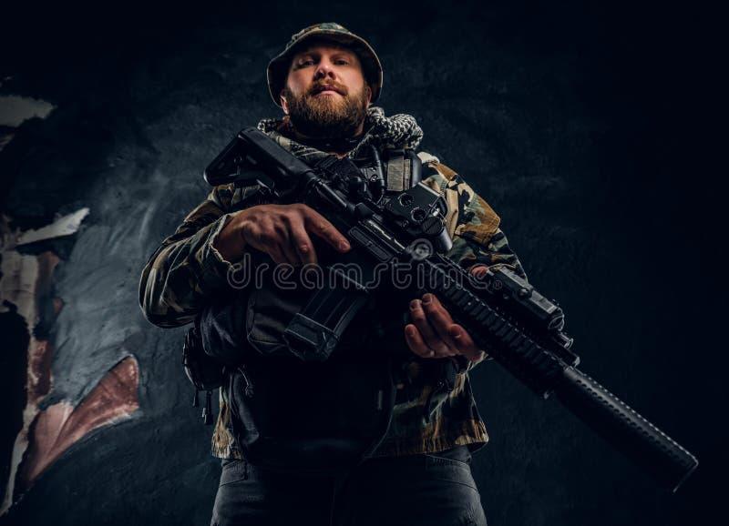 Soldat der besonderen Kräfte in der getarnten Militäruniform, die ein Sturmgewehr hält Studiofoto gegen eine Dunkelheit lizenzfreie stockbilder