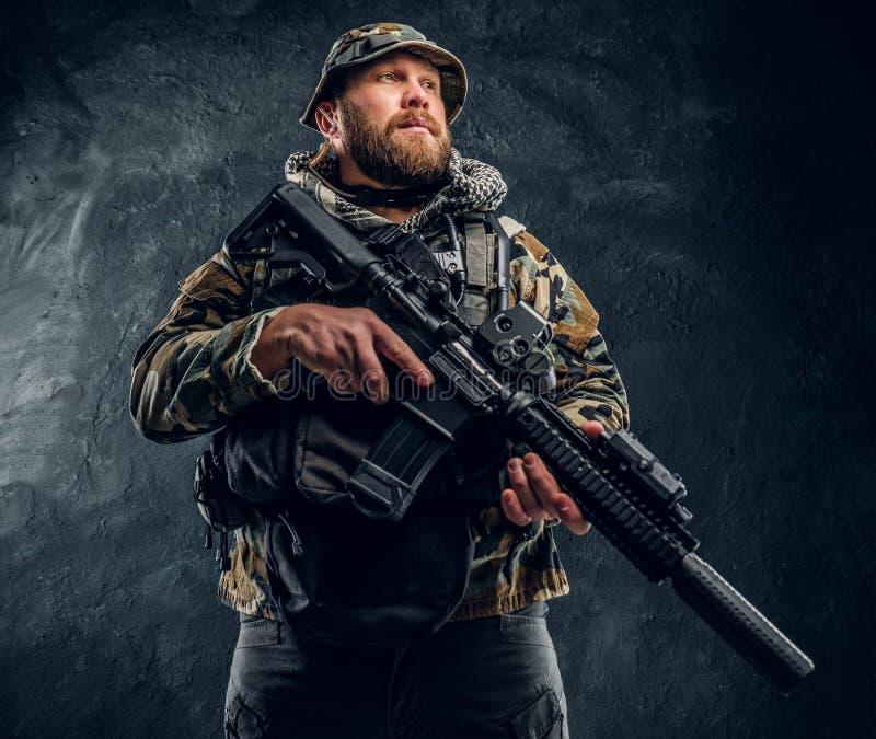 Soldat der besonderen Kräfte in der getarnten Militäruniform, die ein Sturmgewehr hält Studiofoto gegen eine Dunkelheit stockbild