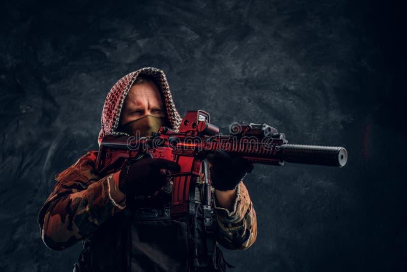 Soldat der besonderen Kräfte in der tragender Maske und Haube der Militäruniform, die ein Sturmgewehr mit einem Laser-Anblick hal stockfotografie