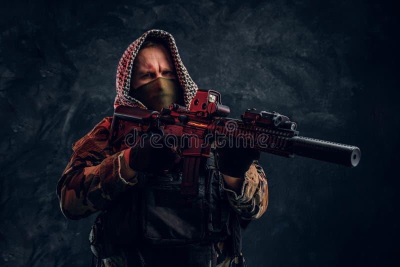 Soldat der besonderen Kräfte in der tragender Maske und Haube der Militäruniform, die ein Sturmgewehr mit einem Laser-Anblick hal lizenzfreie stockbilder