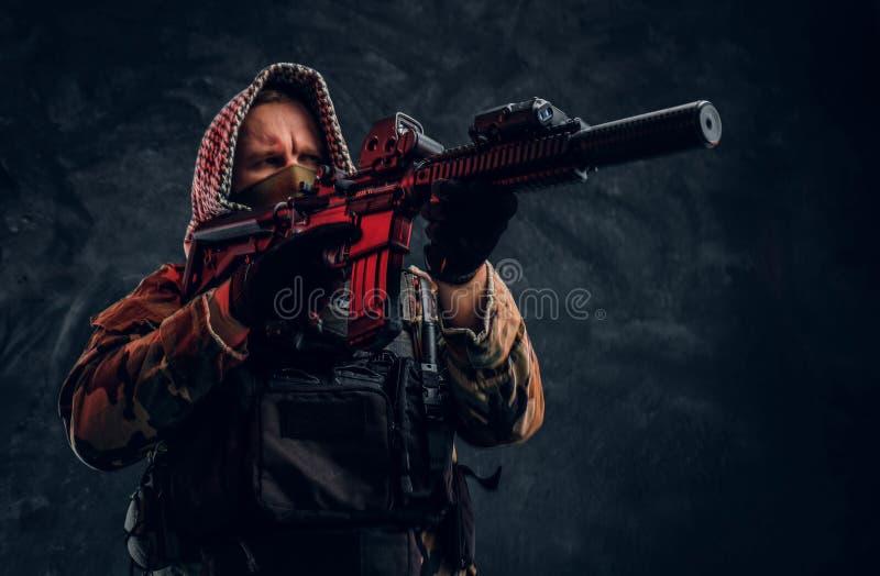 Soldat der besonderen Kräfte in der tragender Maske und Haube der Militäruniform, die ein Sturmgewehr mit einem Laser-Anblick hal stockbild