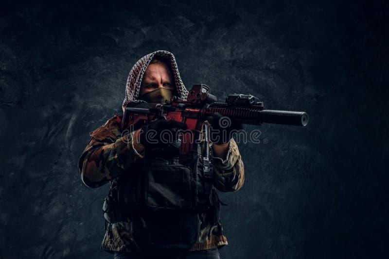 Soldat der besonderen Kräfte in der tragender Maske und Haube der Militäruniform, die ein Sturmgewehr mit einem Laser-Anblick hal stockbilder