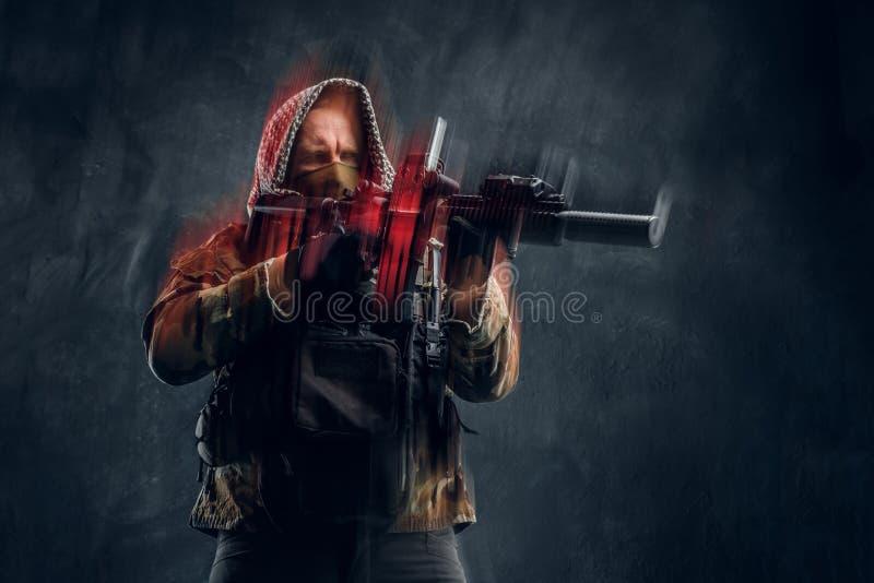 Soldat der besonderen Kräfte in der tragender Maske und Haube der Militäruniform, die ein Sturmgewehr mit einem Laser-Anblick hal lizenzfreies stockfoto