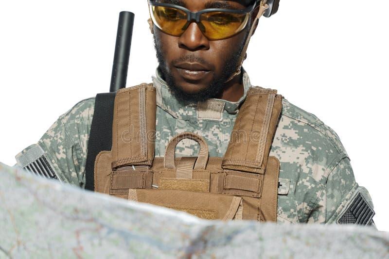 Soldat, der die amerikanische Armeeuniform betrachtet Karte trägt stockbild