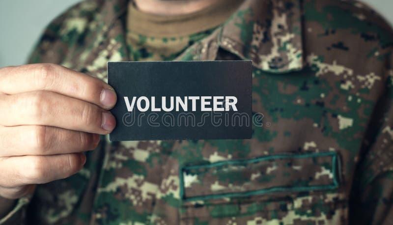 Soldat, der eine Karte mit Text Freiwilligem hält lizenzfreies stockfoto